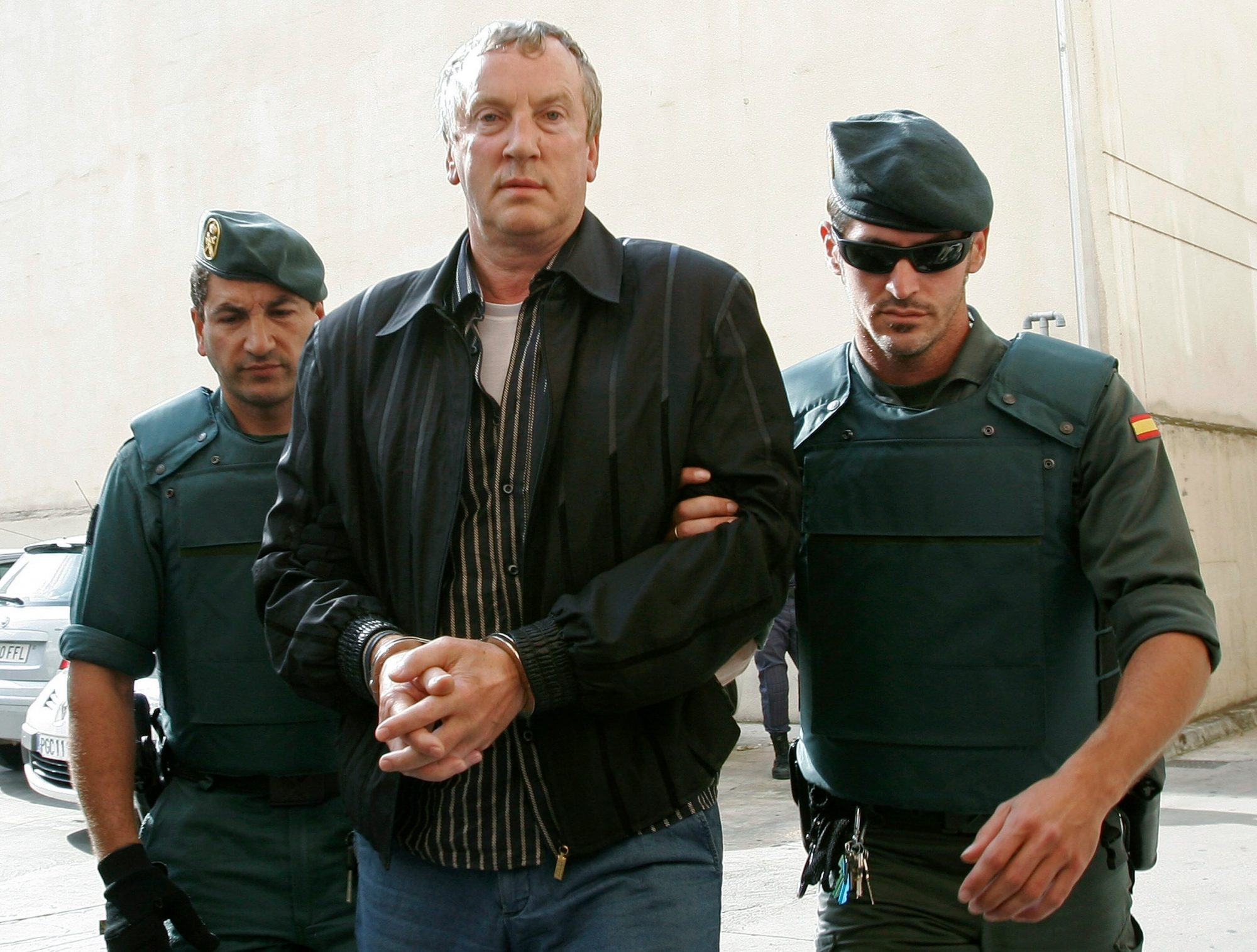 Police officers accompany Gennady Petrov, a mob boss linked to top Russian officials, after his arrest on the island of Mallorca in 2008. Photo credit: Dani Cardona/Reuters