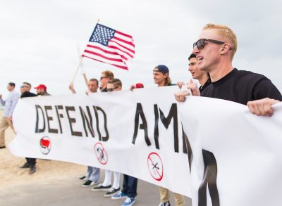 ram members daley nearest at right tyler laube holding an american flag and robert rundo far left display a defend america banner at a pro trump