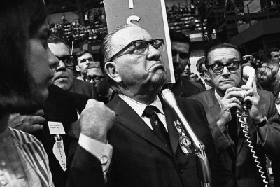 Mayor Richard J Daley Stands At The Microphone During 1968 Democratic National Convention In Chicago While Shouts Resound From Crowd