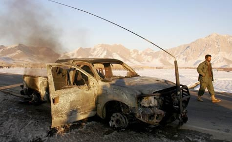 An Afghan policeman walks past a vehicle that had carried U.S. civilian contractors, after it was targeted by a suicide bomber in the Logar province. (Farzana Wahidy/AFP/Getty Images/January 2007 file photo)