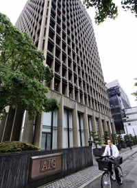 A cyclist passes by the building of insurance giant American International Group (AIG) in Tokyo on May 8, 2009. (Yoshikazu Tsuno/AFP/Getty Images)