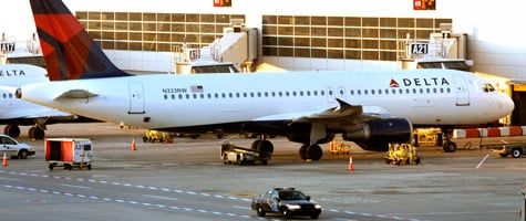 A police car patrols past a Delta jet at the Detroit Metropolitan Airport on Dec. 26, 2009, one day after a Nigerian man allegedly attempted to blow up a different Delta airplane that was landing at the airport by igniting an incendiary device while aboard the aircraft. Homeland Secretary Janet Napolitano has called for increasing the number of federal air marshals in light of that attempted attack. (Bill Pugliano/Getty Images)