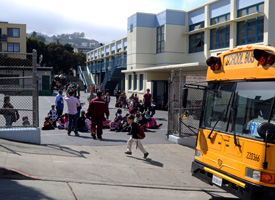 Children at the Harvey Milk Civil Rights Academy prepare to board the bus home after their first day back to school in San Francisco, Calif., on Aug. 24, 2009. (Russel A. Daniels/AP Photo)