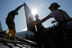 Workers at Mount Rainier National Park in Washington state install solar panels on the roof of the park's Emergency Operations Center as part of a program funded by federal stimulus dollars. (Ted S. Warren/AP Photo)