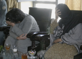 Aafia Siddiqui, right, and her son cover their faces while being shown to the media in Ghazni, Afghanistan. (Credit: AP Photo/File)