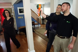 Dave Boettcher, right front, from Next Step Living measures temperatures by infrared readings to reveal energy leaks, as Georgina Fulton Prager, left, and her husband Michael Prager watch at their home in Arlington, Mass. (Robert SpencerAP Photo)