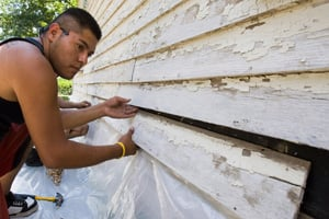 Edwin Aguilar replacing siding during weatherization work on a home in Grafton, Neb., in August. (Nati Harnik/AP Photo)
