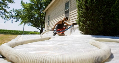 Edwin Aguilar pumps insulation material into a wall during weatherization work on a home in Grafton, Neb., on Aug. 4, 2009. (Nati Harnik/AP Photo)
