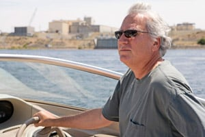 Tom Carpenter, head of the nonprofit watchdog group Hanford Challenge, drives his boat along the Hanford Reach of the Columbia River while pointing out the different reactors on the Hanford Nuclear Reservation. (Jackie Johnston/ProPublica)