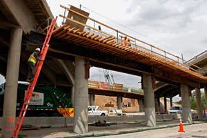 Workers construct a new bridge at 74th Avenue and I-76 northeast of Denver in Commerce City, Colo., on Wednesday, July 29, 2009.  (Ed Andrieski/AP Photo)