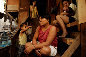 Vicky Buhawe of Cebu city, center, whose partner, Filipino Marcelo Salazar, was killed in Iraq, isn't entitled to benefits under U.S. law. Only their son, John Mark, left, is eligible for $14,000, but there's no record his father's employer reported his death to the U.S. Labor Department. (Francine Orr/Los Angeles Times)