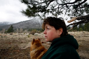 Rita Richardson of Gardnerville, Nev., rests beneath a tree as it begins to snow. She walks to a spot in the mountains near her home where she has shaped a heart in small stones. She feels connected to her late husband Rod Richardson, who was killed in Iraq when his convoy was struck by an IED on Oct. 6, 2006. (Francine Orr/ Los Angeles Times)