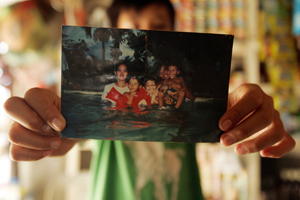 Emerson Torres, 11, holds out a family photograph at his home in San Fernando, Philippines. His father, Rey Torres, was killed in April 2005 in Iraq while working as a contractor. (Francine Orr/ Los Angeles Times)