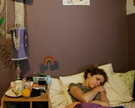 Sara Dill, then 17, lays in her bed. Her father, Wade, took the contractor job in Iraq to start a college fund for her. (Francine Orr/ Los Angeles Times/July 16, 2007)