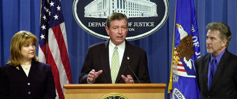 U.S. Attorney General John Ashcroft, center, speaks as Kellie Greene, director of Speaking Out About Rape, Inc., left, and John Walsh, host of America's Most Wanted, listen at the Justice Department on March 11, 2003. Ashcroft discussed President Bush's plans to eliminate the DNA backlog. (Stefan Zaklin/Getty Images)