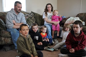 Terry and Desiree Gonyon with six of their nine children, from left to right, Tylar, 7, Kyle, 6, Zachary, 3, Haylee (in Desiree's arms), 1, Aedily, 7, and Michael, 9, at home in the Timber Brook Mobile Home Park in Bristol, Ind., after they lost their home in nearby Elkhart, Ind., to foreclosure on April 8, 2009. (Amanda Rivkin/ProPublica)