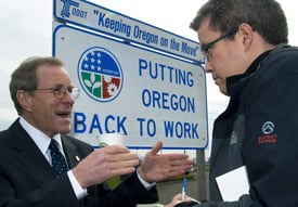 Oregon Governor Ted Kulongoski speaks with a reporter about Oregon's economic recovery efforts at the kickoff of Oregon's first federally funded stimulus project in March. (flickr user OregonDOT)