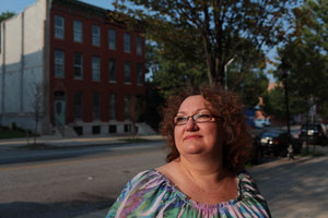 Julie Guy, outside of her dream home in the Union Square neighborhood of Baltimore, Md., in August. She and her husband bought the 140-year-old house, which they planned to restore. They soon discovered extensive water damage, and that, plus health problems, caused them to fall behind on their mortgage. (Melanie Burford/ProPublica)