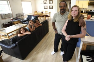 Natalie Simmons and her husband, Stephen, are recent participants in a federal home loan-modification program after refinancing their home four times. They're photographed in their Seward Park neighborhood home along with their daughters Elise, 8, far left, Alexis, 11, and Sunny, 6. (John Lok / The Seattle Times)