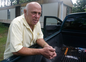 Paul Nelson leans on his truck outside his trailer home in Coden, Ala. (Bill Starling/ProPublica)