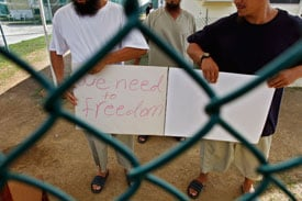 Chinese Uighur Guantanamo detainees, who are cleared for release but with no country to go to, show a home-made note to visiting members of the media, at Camp Iguana detention facility,  on June 1, 2009 at U.S. Naval Base Guantanamo Bay, Cuba. (Photo by Brennan Linsley-Pool/Getty Images, image reviewed by U.S. Military)