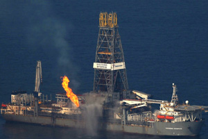 A flare burns from a drill ship recovering oil from the ruptured BP well over the site in the Gulf of Mexico on June 9, 2010. (Photo by Spencer Platt/Getty Images)