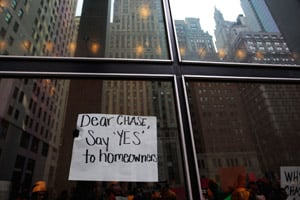 Protesters organized by the Neighborhood Assistance Corporation of America display a sign from inside the lobby of the One Chase Manhattan Plaza building on Dec. 14, 2009, in New York City. (Chris Hondros/Getty Images)