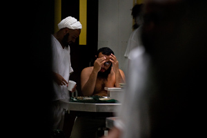 In this photo reviewed by U.S. military officials, detainees gather during lunch in a communal area inside Camp VI at the detention center in Guantanamo Bay, Cuba, on March 30, 2010. (Paul J. Richards/AFP/Getty Images)