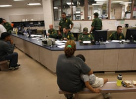 A mother and daughter wait for out-processing at a U.S. Border Patrol station after they were caught crossing from Mexico into the United States on Aug. 7, 2008 near Laredo, Texas. (John Moore/Getty Images)