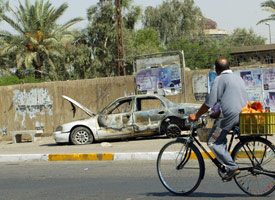 An Iraqi man rides by the remains of a car burnt during the Blackwater shooting in Nisour Square on Sept. 16, 2007. (Credit: Ali Yussef/AFP/Getty Images)
