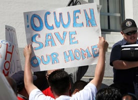 Protesters with community advocacy group ACORN hold signs and surround a man auctioning off foreclosed homes on March 12, 2009 in Oakland, Calif. (Photo by Justin Sullivan/Getty Images)