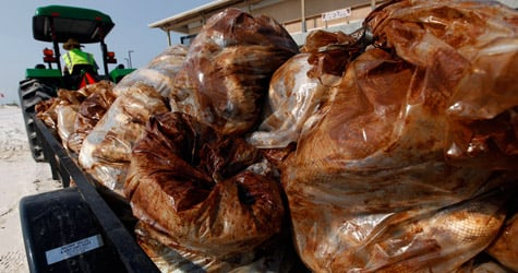A worker hauls away a load of garbage bags filled with oil-soaked booms on June 14, 2010, in Gulf Shores, Ala. (Chris Graythen/Getty Images)