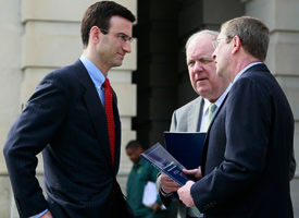 Office of Management and Budget Director Peter Orszag, left, looks on after handing over a copy of the President's Fiscal Year 2010 Budget to Senate Budget Committee Chairman Kent Conrad (D-ND), right, and House Budget Committee Chairman John Spratt (D-SC), second from the right, in front of the Capitol Building on Feb. 26, 2009. (Photo by Mark Wilson/Getty Images)