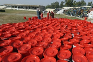 Pakistani workers arranging buckets to be distributed to internally displaced Pakistanis fleeing from military operations. (Aamir Qureshi/AFP/Getty Images)