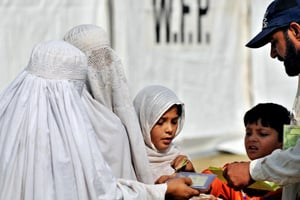A Pakistani NGO employee, right, checking the papers of internally displaced tribeswomen fleeing South Waziristan, outside an aid distribution point in Dera Ismail Khan. (Farooq Naeem/AFP/Getty Images)