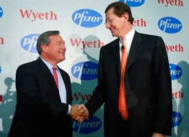 Jeffrey B. Kindler, CEO of Pfizer, left, and Bernard Poussot, CEO of Wyeth, shake hands at a news conference discussing the planned merger of their companies on Jan. 26, 2009 in New York City. (Photo by Mario Tama/Getty Images)