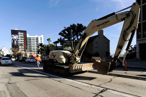 A construction worker stops traffic on Sunset Boulevard as he helps an excavator move where work has began on the Recovery Act-financed $7 million facelift on Jan. 28, 2010, in West Hollywood. (Kevork Djansezian/Getty Images)