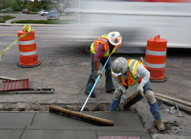 Workers smooth out a new sidewalk at a federal stimulus funded road project on May 21, 2009 in Littleton, Colo. (John Moore/Getty Images)