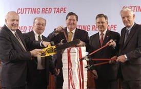 This photo from 2003 shows two regulators: James Gilleran of the Office of Thrift Supervision (holding the chainsaw) and John Reich (then Vice Chairman of the FDIC and later at the OTS, second from right), along with  representatives of three banker trade associations. (FDIC/OTS file photo)