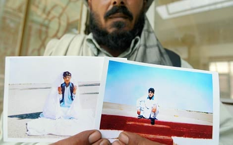 An Afghan man, Gul Nak, the uncle of Guantanamo Bay prisoner Mohammed Jawad, poses with pictures of Jawad in Kabul on June 1, 2009. The Obama administration had volunteered to end Jawad's widely criticized detention. (Shah Marai/AFP/Getty Images).