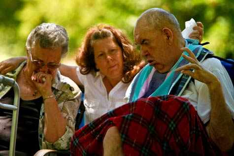 Mother Dorothy Turpen (left) and caregiver Bev Glasgow sit next to Reggie Lane during a memorial service for his wife, Linda, in July 2009. Linda had been hospitalized after suffering respiratory distress. Under the shade of scrub oak and aspen, Reggie watched as Linda's family and friends sang 'Amazing Grace' and looked at old photos of the couple.  (Francine Orr / Los Angeles Times)