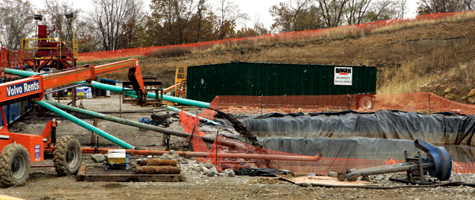 Fluids made up of a combination of naturally occurring water from the shale formation and drilling mud are pumped into a lined retaining area behind the drilling rig on a farm in Houston, Pa., in October 2008. New York state is currently holding a public comment period for an environmental review of natural gas drilling in the Marcellus Shale. (Keith Srakocic/AP Photo)