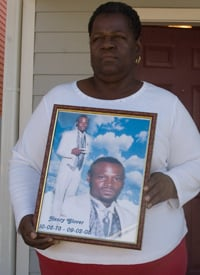 Edna Glover holds a portrait of her son, whose charred remains were found behind a police station. (Credit: Chandra McCormick & Keith Calhoun)
