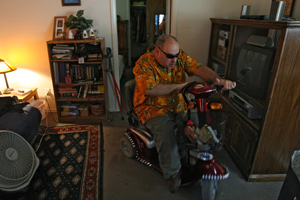 Peter Lloyd drives his scooter towards the front door as he prepares to depart his home in St. Charles for his job in Chesterfield, Mo., Friday afternoon.  Lloyd leads a more independent life by living in his own home, driving himself to work in a car, and shopping now that he is no longer in a nursing home. (John L. White/St. Louis Post-Dispatch)