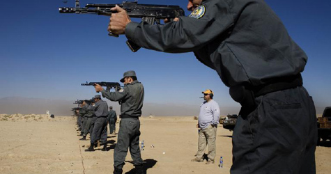 A DynCorp employee, in the background, oversees a rifle course for Afghan police at a military range east of Kabul. (Max Becherer/Polaris)