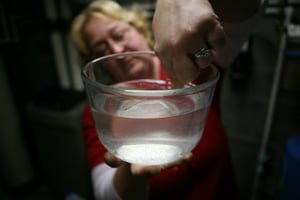 Julie Sautner, of Dimock, Pa., seen here in her basement with her new water filtration system, flushed her toilet one day to find a rush of earth-brown water. Tests showed her drinking water was high in aluminum, iron and methane. (Abrahm Lustgarten/ProPublica)