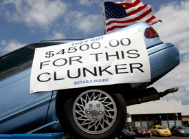 A vehicle sits in a dumpster on display in front of Bill Wink Chevrolet dealership to attract customers in for the cash for clunkers program in Dearborn, Mich., Aug. 6, 2009. (Rebecca Cook / Reuters)