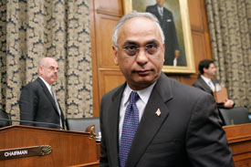 Deven Sharma, president of Standard & Poor's, leaves after talking to Committee Chairman Rep. Henry Waxman. (Molly Riley / Reuters )