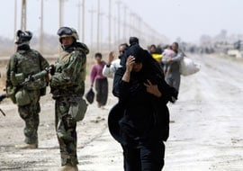 A Baghdad refugee walks next to a U.S Marine, Apr. 5, 2003. (Reuters/Oleg Popov)