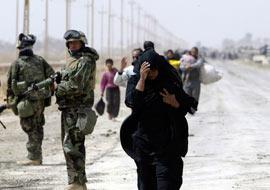 A Baghdad refugee walks next to a U.S Marine, Apr. 5, 2003. (Reuters/Oleg Popov)